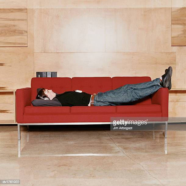 Man Sleeping Lying on a Sofa With His Eyes Closed, Listening to Headphones