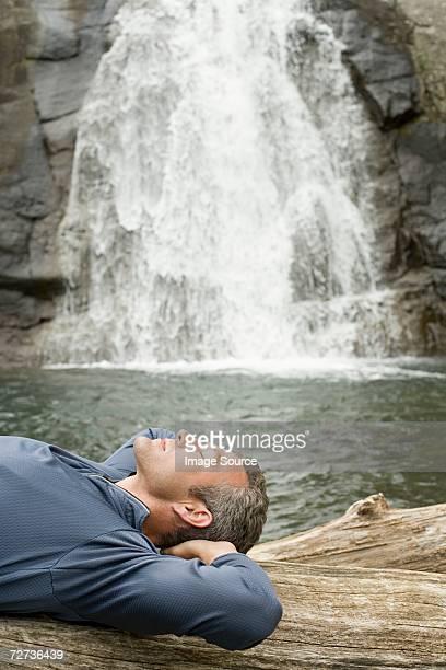 Uomo di dormire nei pressi di una cascata