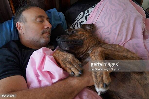 Man Sleeping On A Bed With His Dog