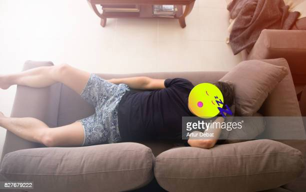 Man sleeping on a sofa with sleepy emoticon on his face taken from elevated viewpoint in a picture merging illustration and humor with famous cool faces used for texting.