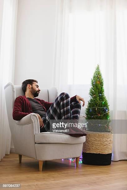 Man sleeping on armchair at home at Christmas time