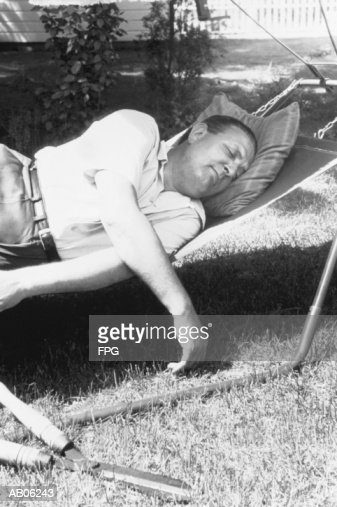 Man sleeping on cot in garden, hedge shears on lawn (B&W) : Stock Photo