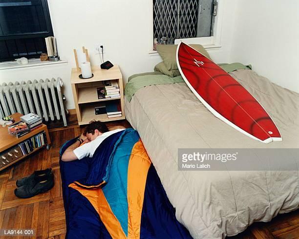 Man sleeping on floor, surfboard on bed