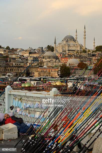 Man sleeping on Galata Bridge with fishing rods over Golden Horn with Suleymaniye Mosque Istanbul