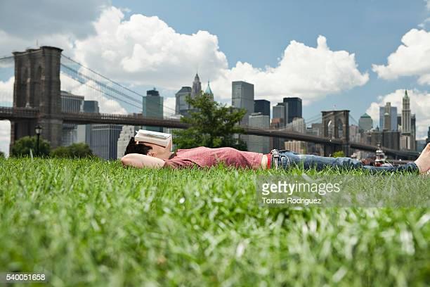 Man sleeping on grass in front of skyline, New York City, USA