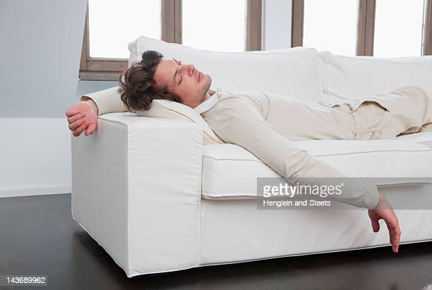 Homme dormir sur le canapé dans la salle de séjour