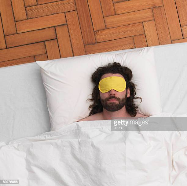 Man sleeping, wearing eye-mask