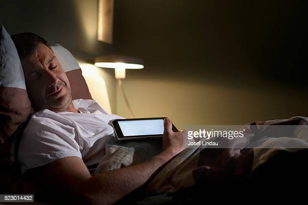Man sleeping with digital tablet on chest
