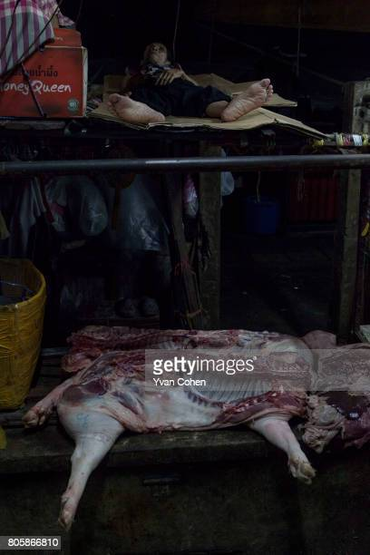 A man sleeps above the carcass of a slaughtered pig in a market in the Chinatown district of Bangkok