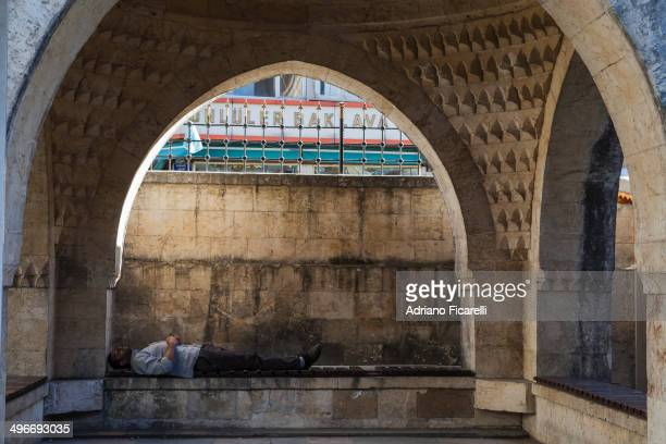 CONTENT] A man sleeps after a night passed under a mosque