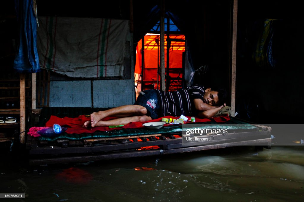 A man sleeps as flood waters lap beneath his make-shift bed, as major floods hit North Jakarta on January 20, 2013 in Jakarta, Indonesia. The death toll has risen to at least 21 since severe flooding struck the city on July 17. The US has offrered US$150,000 (Rp 1.44 billion) in aid.