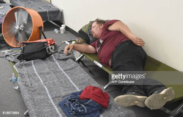 A man sleeps at an evacuation center in Oakhurst California on July 19 2017 The Detwiler fire has so far burned more than 45000 acres and destroyed...