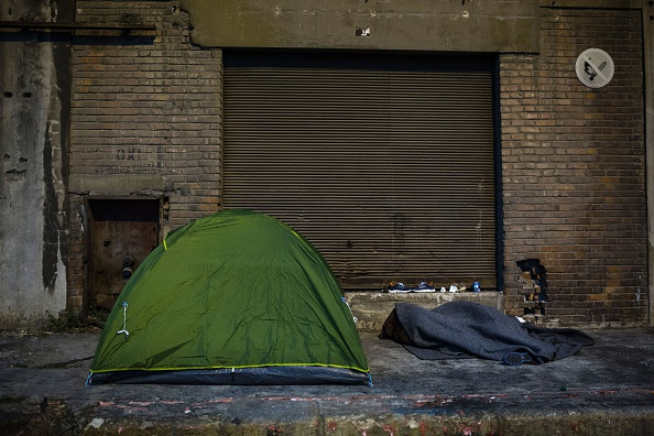 A man sleeps beside a tent outside a migrant and refugee makeshift camp inside a building at Piraeus harbour in Athens, on March 6, 2016
