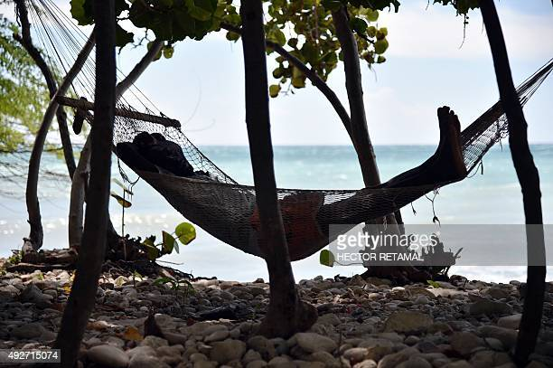 A man sleeps in a hammock close to the beach in the commune of is AnseaPitres in the South East Department of Haiti on October 14 2015 AFP...