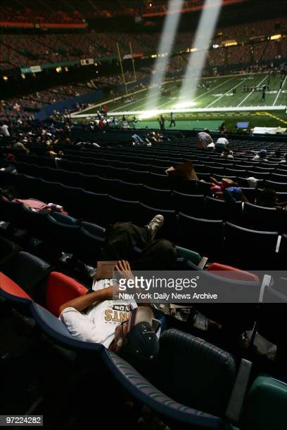 A man sleeps in the stands of the Superdome in New Orleans Louisiana where some 25000 refugees have taken shelter after Hurricane Katrina devastated...