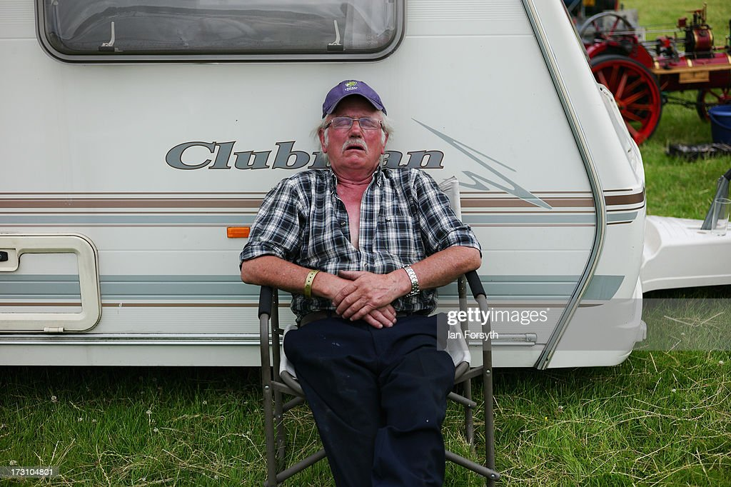 A man sleeps in the warm afternoon at the steam rally at Duncombe Park on July 7, 2013 in Helmsley, England. The popular steam rally takes place in the magnificant grounds of the park over the first weekend of July each year and brings together traction engines, working displays, vintage tractors, commercial and military vehicles, vintage cars and motorcycles.