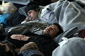 A man sleeps inside a passenger terminal at the port of Piraeus upon the arrival of migrants and refugees aboard the Blue Star 1 passenger ship from...