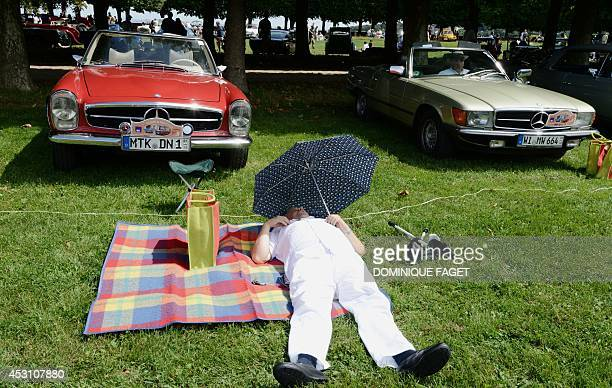 A man sleeps near classic Mercedes during the 7th classic cars crossing of Paris at Meudon's observatory park on August 3 2014 AFP PHOTO/DOMINIQUE...