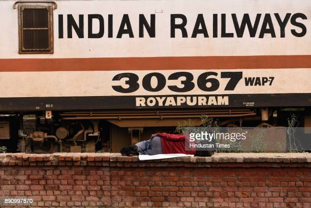 A man sleeps next to the moving train on a cold morning at Nizamudin railway station on December 12 2017 in New Delhi India