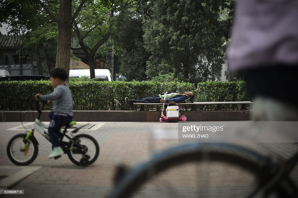 A man sleeps on a bench along a road in Beijing on April 29, 2016. / AFP / WANG