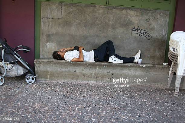 A man sleeps on a bench as Puerto Rican Governor Alejandro Garcia Padilla addresses the island's residents in a televised broadcast regarding the...