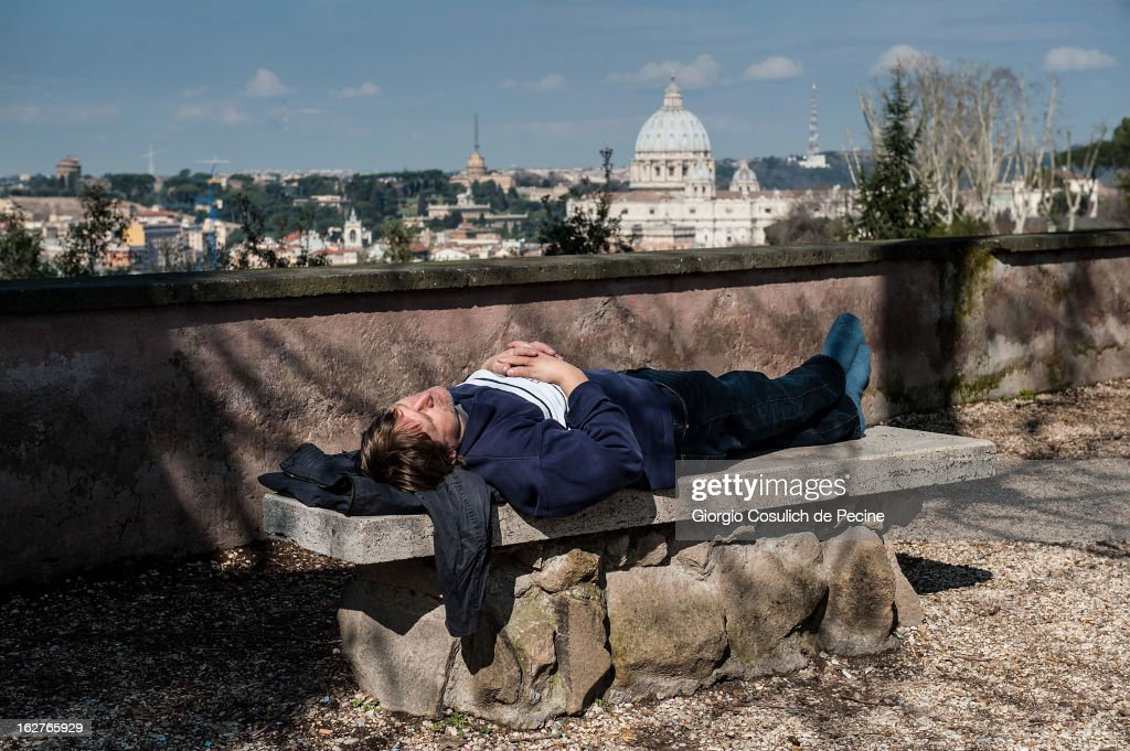 A man sleeps on a bench as the dome of St. Peter is seen from Gianicolo on February 26, 2013 in Rome, Italy. The Pontiff will hold his last weekly public audience on February 27, 2013 before he retires the following day. Pope Benedict XVI has been the leader of the Catholic Church for eight years and is the first Pope to retire since 1415. He cites ailing health as his reason for retirement and will spend the rest of his life in solitude away from public engagements.