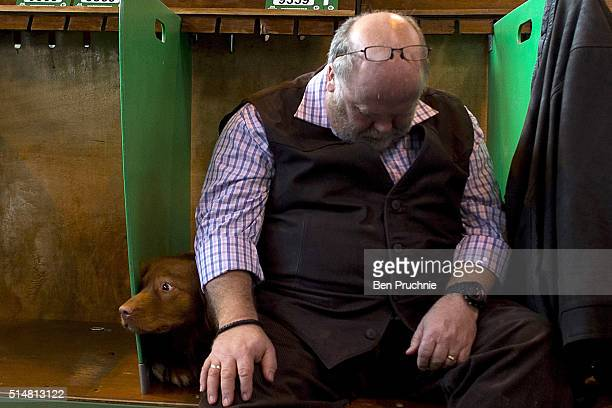 A man sleeps on a bench next to his weimaraner during the second day of Crufts Dog Show on March 11 2016 in Birmingham England First held in 1891...