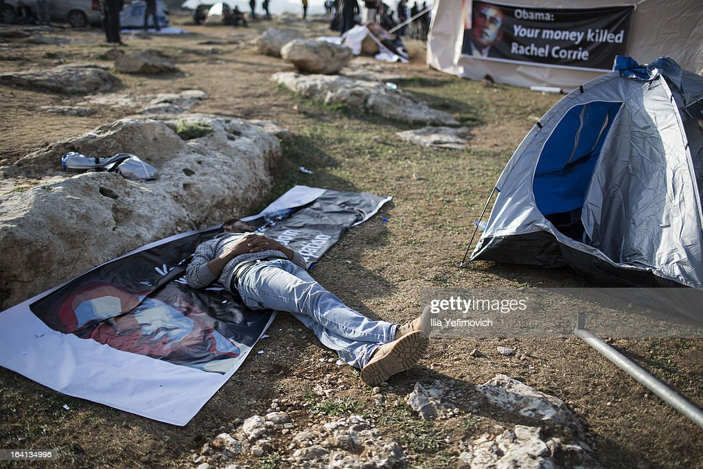 MA'ALE, ADUMIM, WEST-BANK - MARCH 20: A man sleeps on a Obama poster as Palestinians erect protest tents in a camp on March 20, 2013 in the E1 area next to Ma'ale Adumim. The action took place at the same time as U.S. President <a gi-track='captionPersonalityLinkClicked' href=/galleries/search?phrase=Barack+Obama&family=editorial&specificpeople=203260 ng-click='$event.stopPropagation()'>Barack Obama</a> arrived to Ben Gurion airport near Tel Aviv. This will be Obama's first visit as President to the region, and his itinerary will include meetings with the Palestinian and Israeli leaders as well as a visit to the Church of the Nativity in Bethlehem.