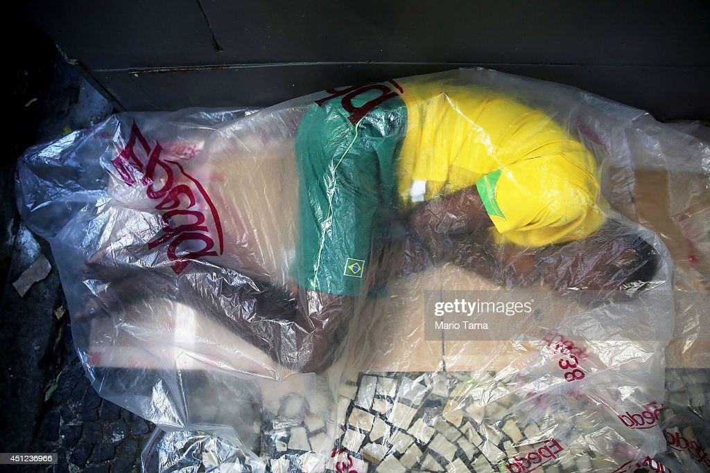 A man sleeps on a sidewalk in Copacabana while dressed in Brazil colors on June 25, 2014 in Rio de Janeiro, Brazil. Economic challenges are visible in the streets of Rio.