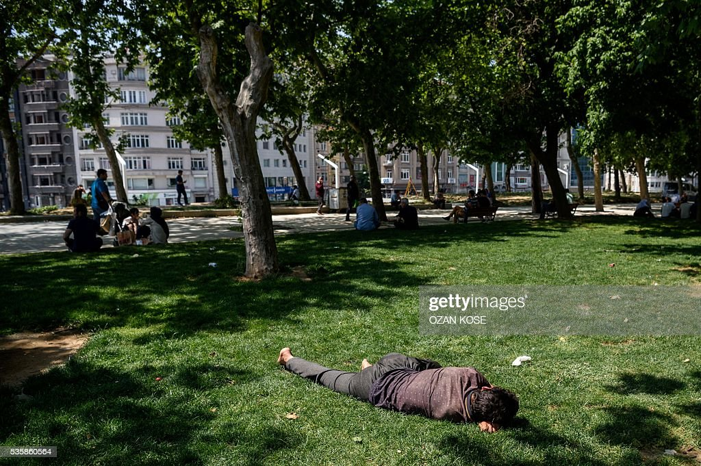 A man sleeps on grass at the Gezi Park on May 30, 2016 in Istanbul, on the eve of the 3rd anniversary of the so-called Gezi Park protests. / AFP / OZAN