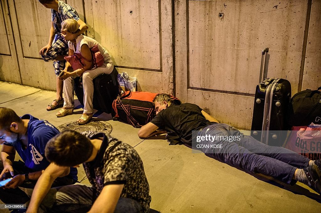 A man sleeps on the ground as people wait with their luggage outside the Ataturk airport in Istanbul, on June 28, 2016, after two explosions followed by gunfire hit the Turkey's biggest airport, killing at least 10 people and injured 20. All flights at Istanbul's Ataturk international airport were suspended on June 28, 2016 after a suicide attack left at least 10 people dead and 20 others wounded, Turkish television stations reported. / AFP / OZAN