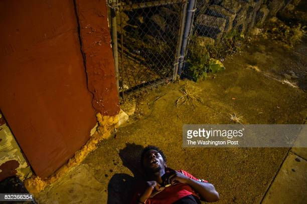 A man sleeps on the sidewalk across from The Last Stop on Thursday July 20 in Philadelphia PA
