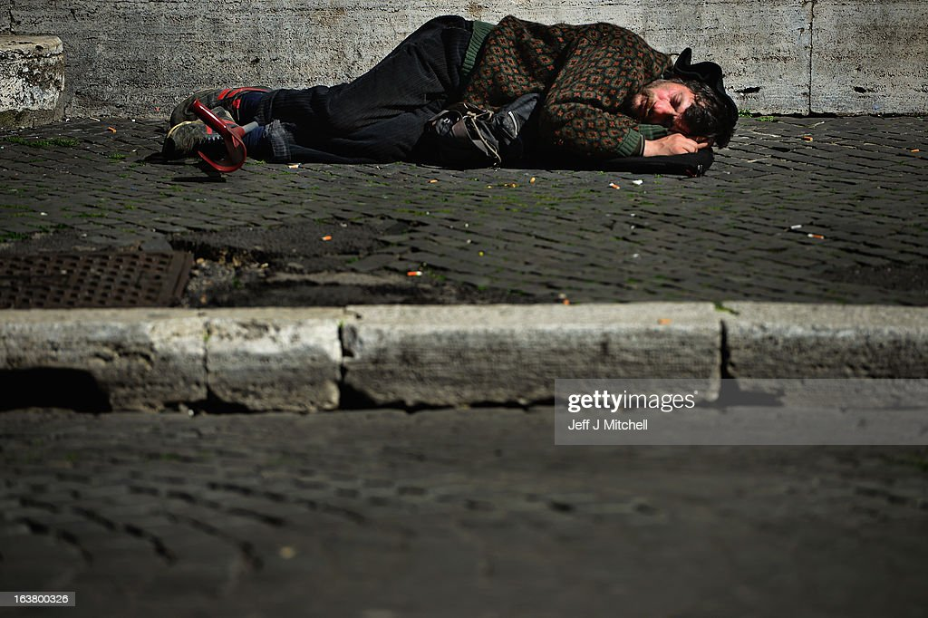 A man sleeps on the street in Piazza Navona on March 16, 2013 in Rome, Italy.Rome is preparing for the inauguration mass of Pope Francis on March 19th.