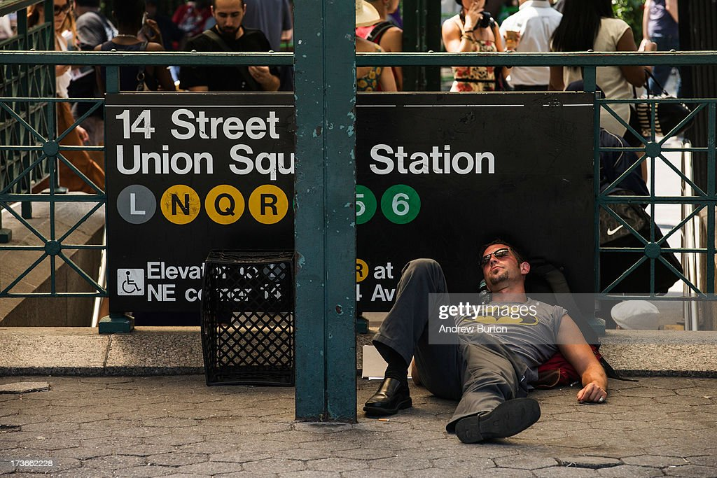 A man sleeps under a Subway entrance's awning at Union Square on July 16, 2013 in New York City. A stifling heat wave has descended upon the New York City region for the week; temperatures are expected to reach into the 100s.