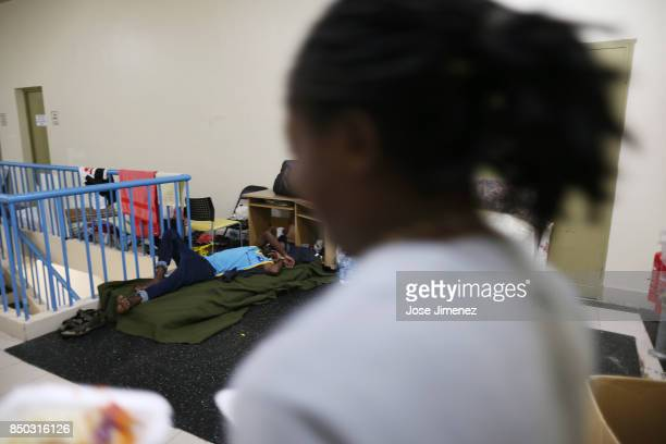 A man sleeps while a woman carries food at a shelter in the Sir Vivian Richards Cricket Stadium on September 20 2017 in North Sound Antigua and...