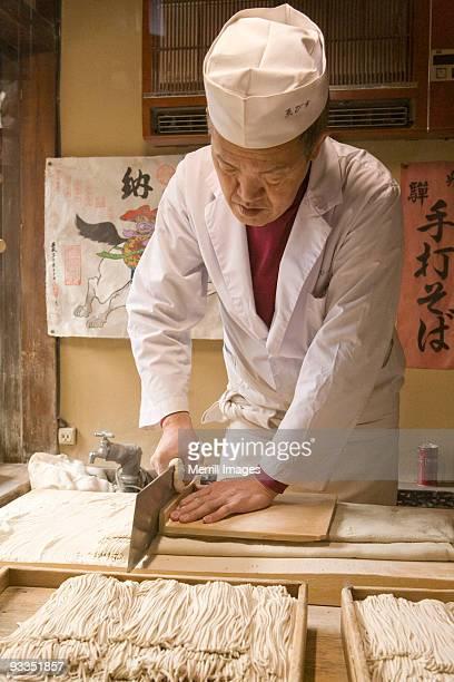 man slicing dough to make soba noodles