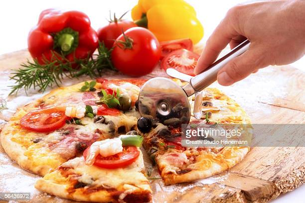 Man slicing pizza with wheel cutter