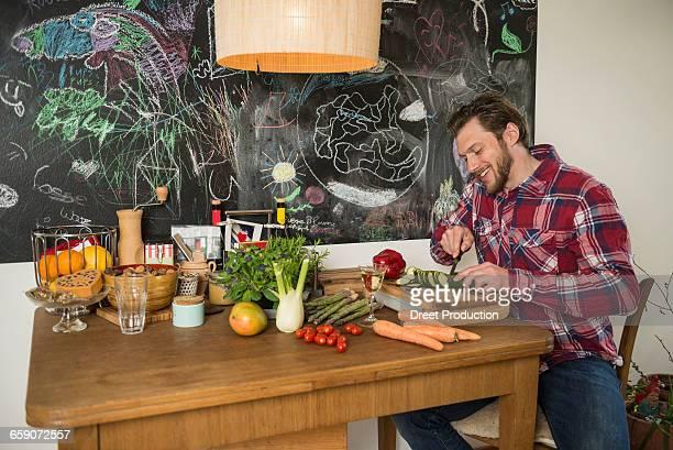 Man slicing vegetables on chopping board, Munich, Bavaria, Germany