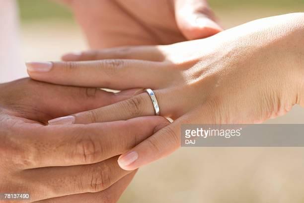 Man sliding ring on woman's finger, Saipan