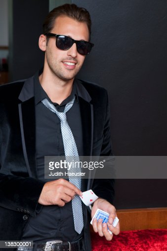 Man slipping cards up his sleeve : Stock Photo