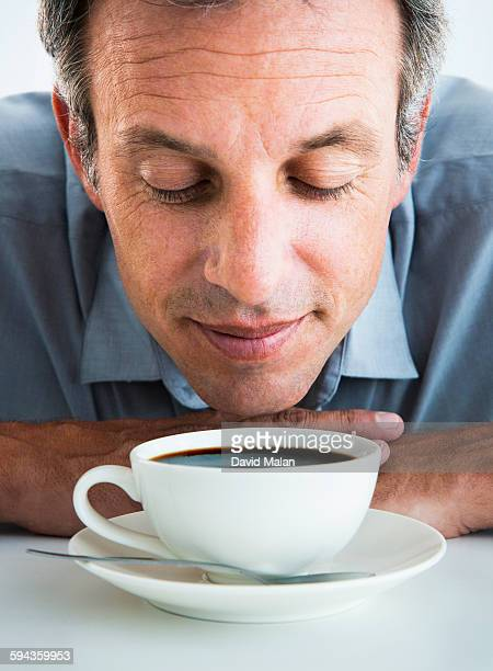 Man smelling a cup of coffee
