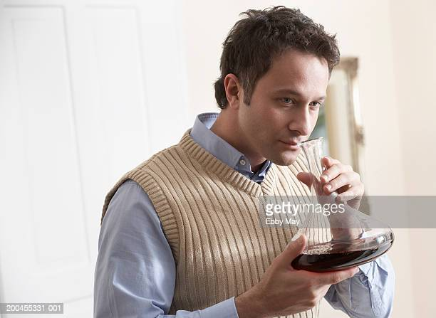 Man smelling bouquet of red wine in decanter, close-up