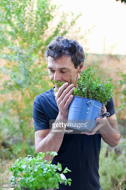 man smelling fresh herbs