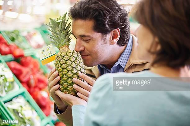 Man Smelling Pineapple