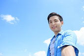 man smile happily and take a selfie with blue sky, asian