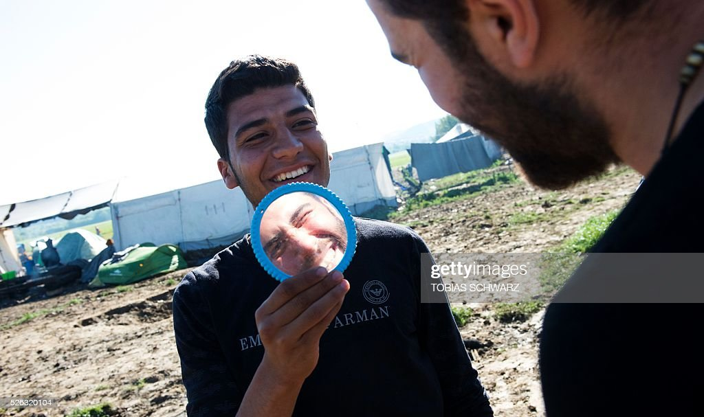 A man smiles and holds a mirror up for another as he shaves at a makeshift camp for migrants and refugees near the village of Idomeni, not far from the Greek-Macedonian border, on April 30, 2016. Some 54,000 people, many of them fleeing the war in Syria, have been stranded on Greek territory since the closure of the migrant route through the Balkans in February. / AFP / TOBIAS