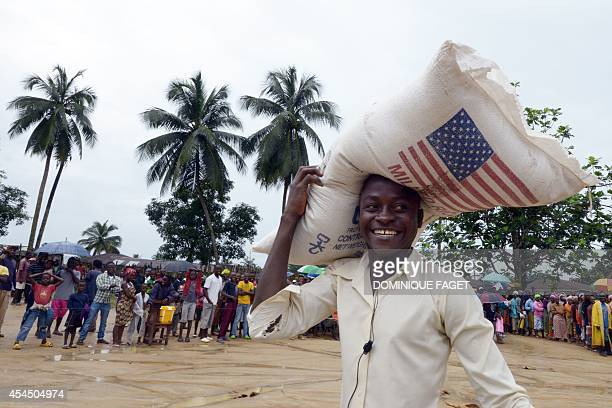 A man smiles as he carries a bag of rice while others wait during a food distribution by the World Food Programme in Dolo's Town some 60 km east of...