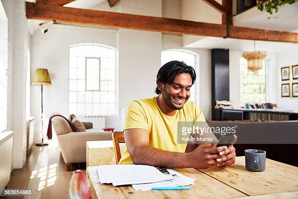 A man smiles whilst using his phone at home