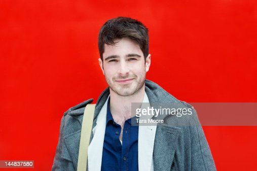 man smiling against red background
