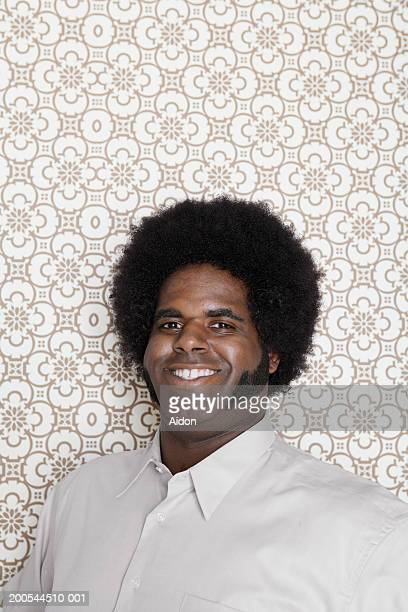 Man smiling, against wallpaper background, portrait